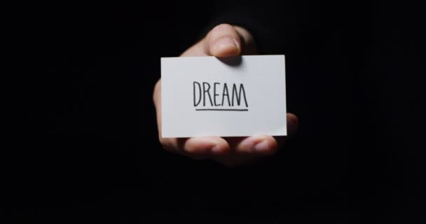 video, partial view of hand showing small paper card with message dream