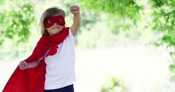Cinemagraph videó a kisgyermek lány, mint szuperhős és mozgó fák a háttérben