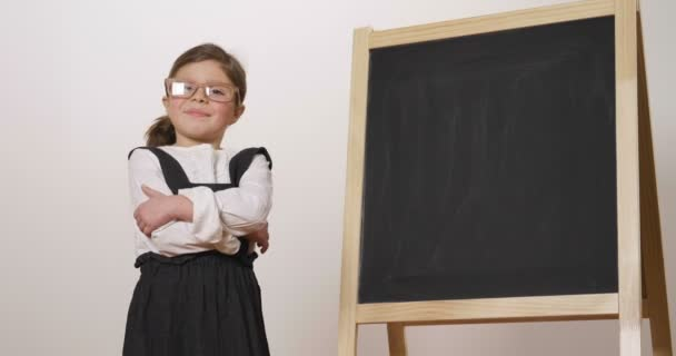 Šťastná dívka oblečená jako učitel před malé tabule drží ruce složené a úsměvy. Koncept: vzdělávací, škola, obchod a lásku k studiu.