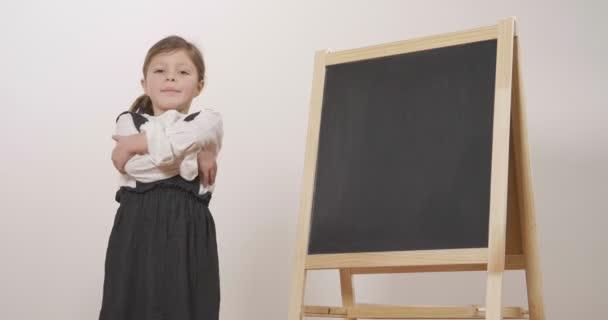 Egy boldog lány felöltözött mint egy tanár, előtt egy kis tábla rendelkezik vele karba tett kézzel és mosolyog. Fogalma: oktatási, iskolai, üzleti és a szeretet, a tanulmány.
