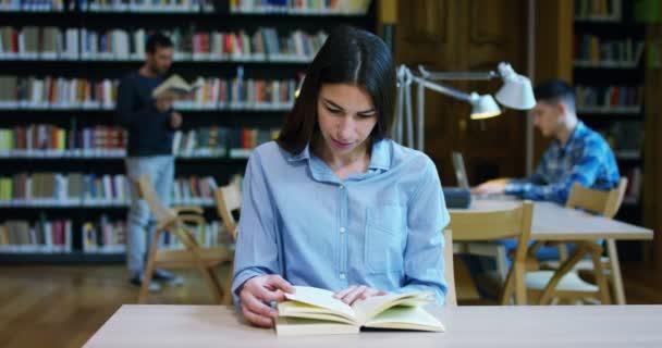 studenti v knihovně ve škole používají počítač a mluvit na projekty