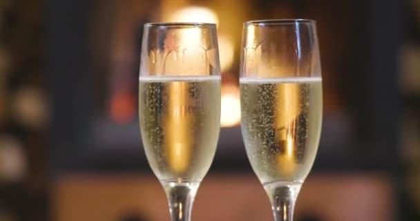 an einem Winterabend sitzt ein Paar entspannt vor dem Kamin, trinkt ein Glas Champagner und stößt an, um zu feiern, während es die Wärme des Kamins genießt.
