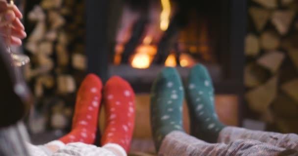 An einem Winterabend sitzt ein Paar entspannt vor dem Kamin, trinkt ein Glas Wein und stößt an, während es die Wärme des Kamins genießt. Konzept von: Urlaub, Entspannung, Wein.