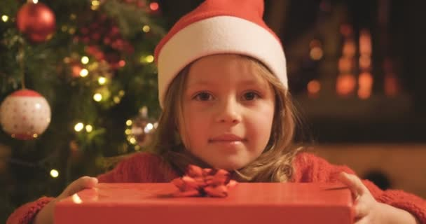 video of cute little Caucasian girl opening gift box at Christmas tree