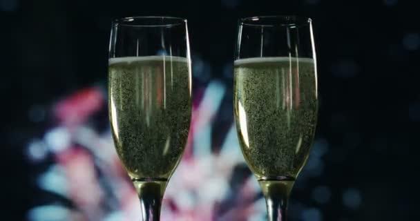 Ein Champagner stößt an, während im Hintergrund das Feuerwerk zündet. Konzept: Neujahr, Liebe, Urlaub, Party.