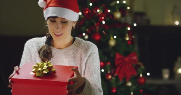 video of happy woman in Santa hat opening gift box at Christmas tree in new year