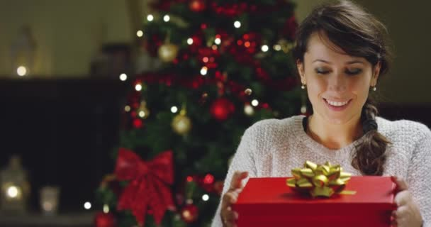 video of happy woman opening gift box at Christmas tree in new year