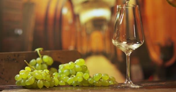 Sommelier im Weinberg schenkt italienischen Weißwein im Glas in Zeitlupe ein
