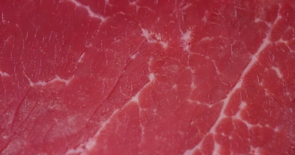 Krásné šťavnaté maso steak na stůl s sůl, rozmarýn, česnek a rajče na černém pozadí, pohled shora. Koncepce: čerstvé  přírodní produkty, bio výrobky, masné výrobky, organické, výživa.