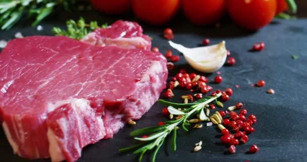Beautiful juicy fresh meat steak on a table with salt, rosemary, garlic, and tomato on a black background, top view. Concept: fresh  natural products, bio products, meat products, organic, nutrition.
