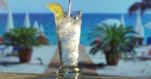 Gießen Cocktail nicht alchoolic in der Nähe des Meeres auf dem Hintergrund der tropischen Insel in Zeitlupe