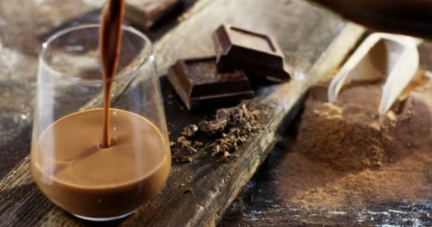 Ruční lití mléka a kakaa ve sklenici, v pomalém pohybu, se šlehačkou a čokoládou vločky, typické zimní nápoj. pozadí, tmavé čokolády a kakaový prášek