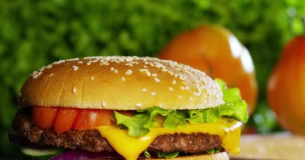 zpomalené video hamburger s cibulí, rajčaty, zelený salát a omáčky
