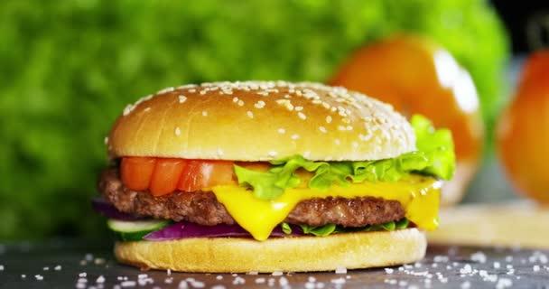 video z americký hamburger s cibulí, rajčaty, zelený salát a omáčky