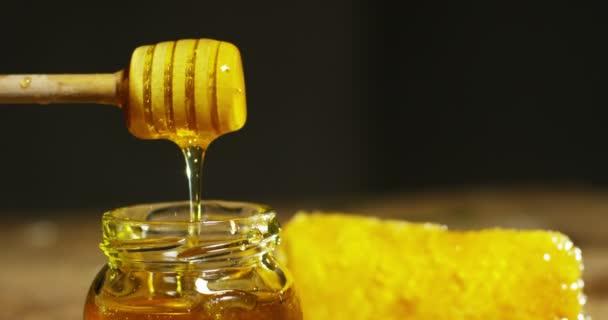 biologické a pravý med nekape uvnitř sklenice. Já plástev medu kape. černé pozadí a dřevěný stůl. zlato padá v slowmotion a udělali to medonosnou z Austrálie.