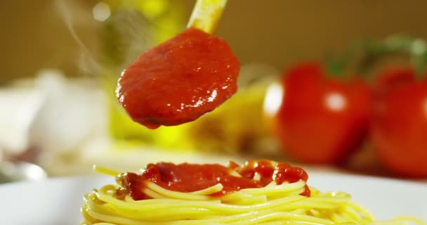 video of hot cooked spaghetti, adding red tomato sauce from spoon