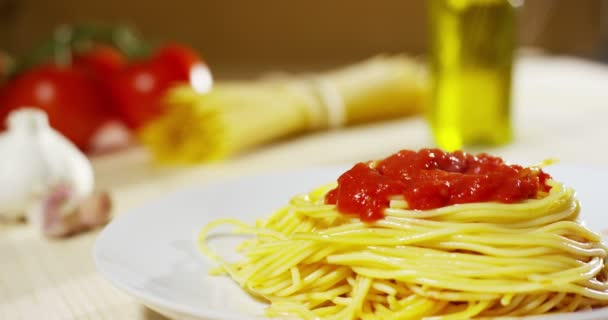 video of hot appetizing cooked spaghetti with red tomato sauce in plate on table