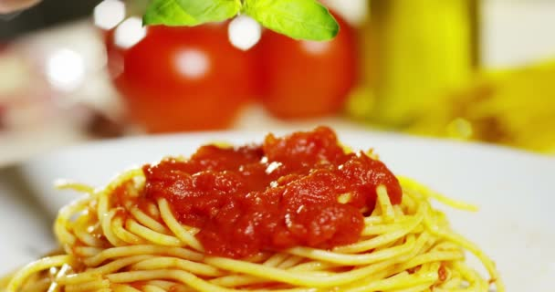 video of appetizing cooked spaghetti with red tomato sauce, slow motion person adding green basil leaves on top