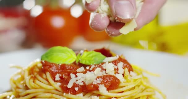 video of appetizing cooked spaghetti with red tomato sauce and adding Parmesan cheese