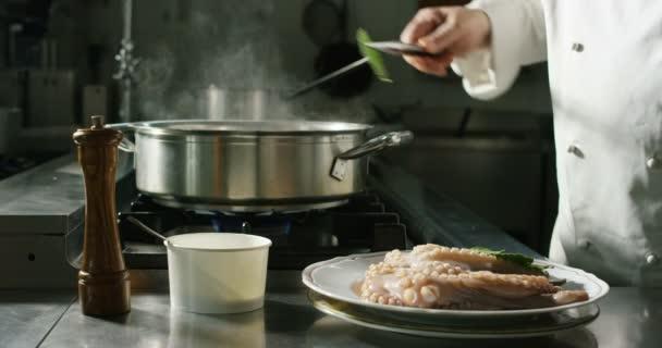 lassított videó a szakács főzés polip a konyhában, amivel zöld gyógynövény levelek levesben a serpenyőben sütőben