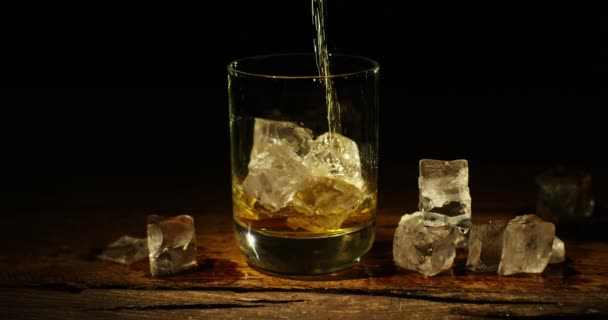 videó a whiskey-t öntenek a pohárba jeget a fából készült asztal