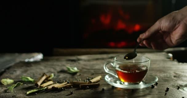 krásná romantická skladba bylinkové čaje a čaje, zatímco se vylévá na staré dřevěné krájecí deska s kořením v pozadí a krb
