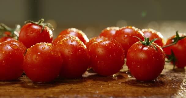 Video von frisch nass gewaschenen roten Tomaten auf Holztisch