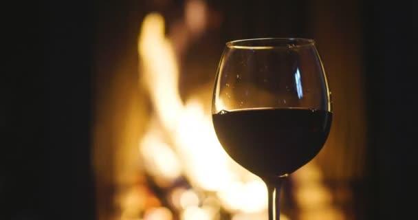 im Winter, vor dem Kamin, wird eingeschenkt, Rotwein in einem Glas verkostet. Konzept von: entspannen, Restaurant, Wein, Somelier.