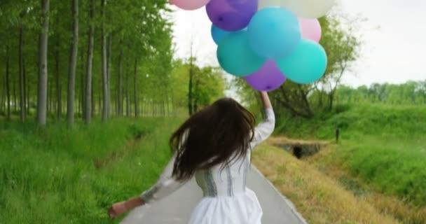 video al rallentatore di donna felice che funziona con gli aerostati variopinti sulla strada nella foresta
