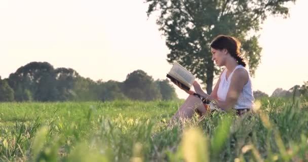 video of woman sitting on green field meadow and reading book