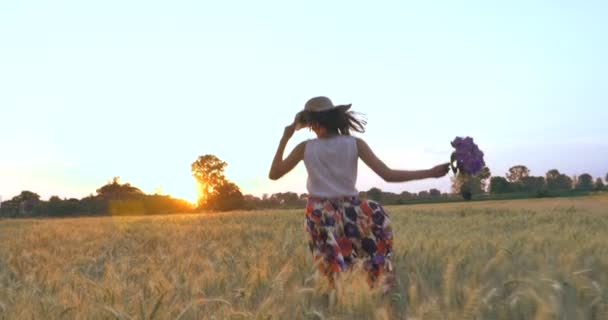 woman running in wheat field with purple flowers, countryside nature and landscape