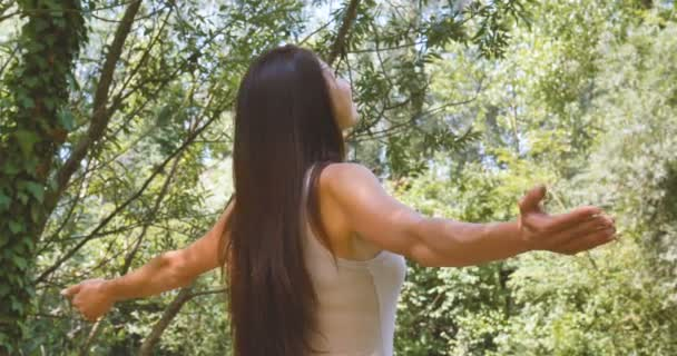 brunette woman spreading hands in forest, harmony and environment concept