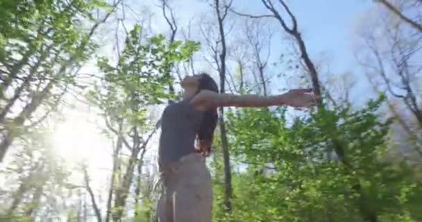 Blick von unten auf brünette freie Frau, die Hände im Wald spreizt, Harmonie und Umweltkonzept
