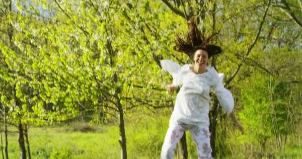 playful happy woman jumping outdoors, slow motion video