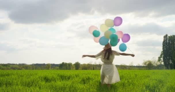 zpomalené video krásné ženy v šatech a klobouk s barevné balónky v louce