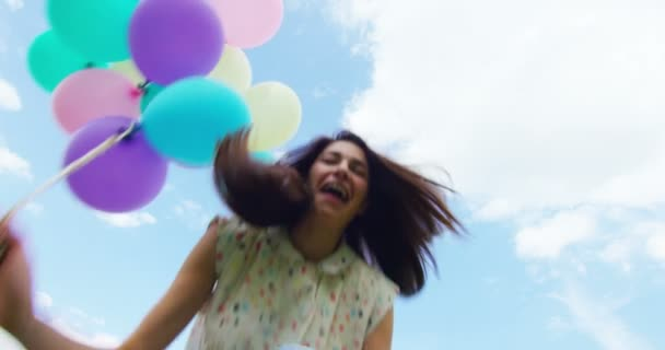 slow motion video of happy woman celebrating and jumping with colorful balloons, bottom view