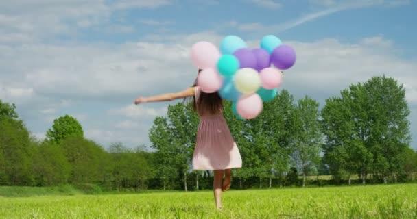 Zeitlupenvideo einer glücklichen Frau, die mit bunten Luftballons feiert