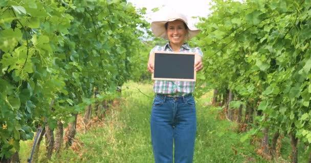 farmer woman standing in grape field plantation and showing empty blackboard for copy space