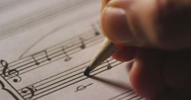 Video, Nahaufnahme eines Musikers, der Melodietöne für ein Lied auf Papierbogen schreibt, Zeitlupenvideo