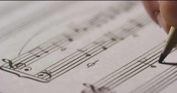 zpomalené video, zblízka střílel hudebník osoby psaní poznámek melodie písně na list papíru