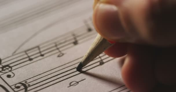 Video, close up shot of musician person writing melody notes for song on  paper sheet with pencil