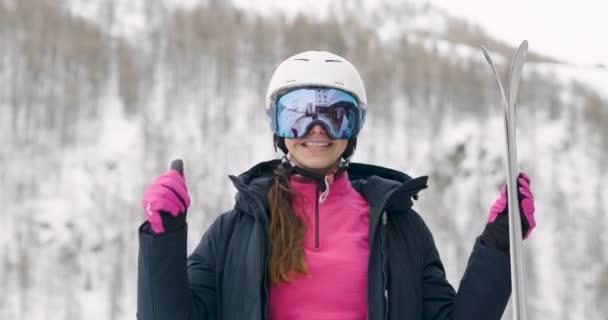 video z ženy v zimě nošení ochranné helmy a lyžařské brýle, držení lyží a ukázal palec nahoru