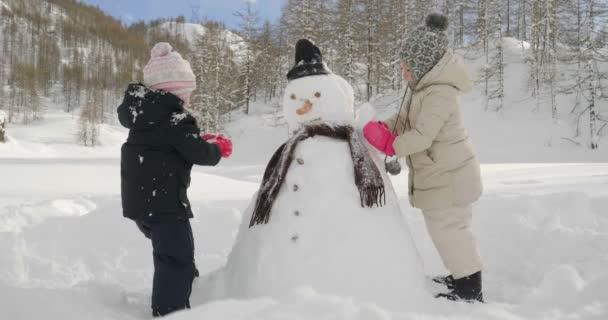Jednoho zimního dne, na horách sníh dvě holčičky hrát a hrát sněhulák. Koncept: Zimní dovolená, hora hry, Vánoce,