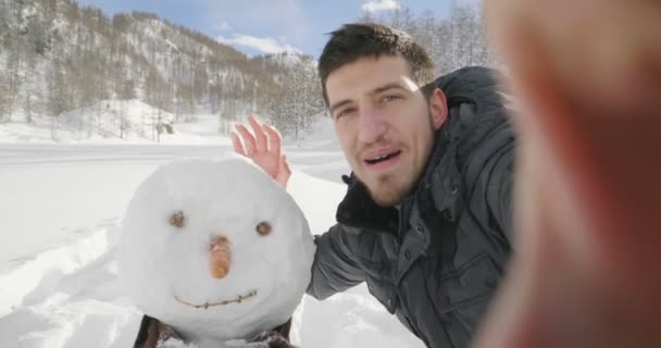 Man standing beside snowman and making video call against mountains