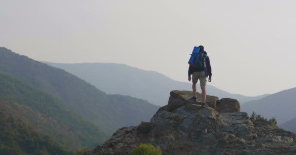 video of traveler man hiking on rocky mountain peak and spreading hands