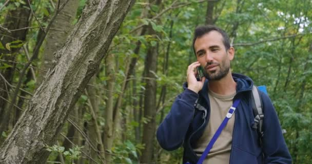 slow motion video of hiker traveler man talking on mobile phone in forest and smiling