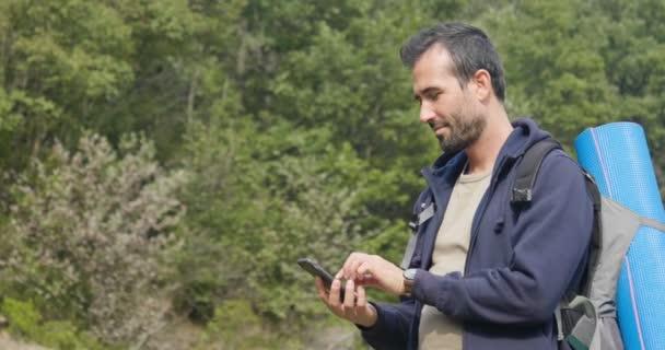 zpomalené video turista cestující muže stojí v přírodě a pomocí mobilního telefonu