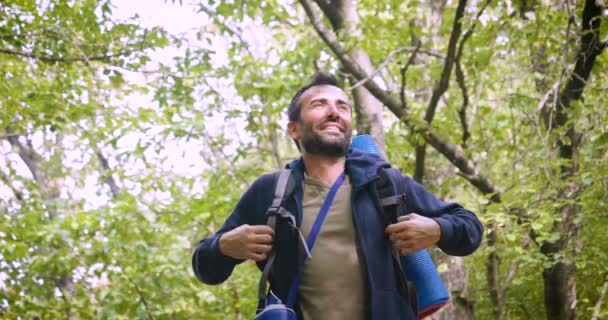 video of hiker traveler man in forest spreading hands and holding blue water bottle