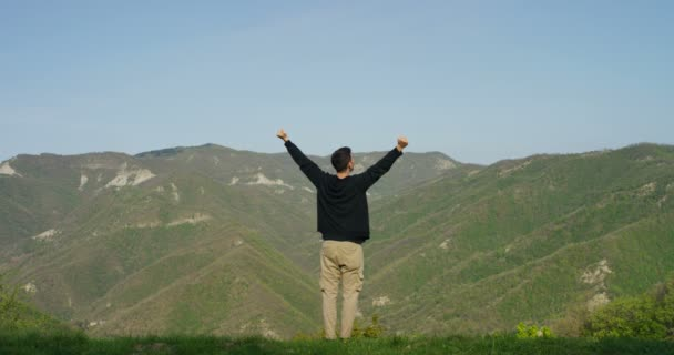 video of traveler man standing and looking at summer mountains