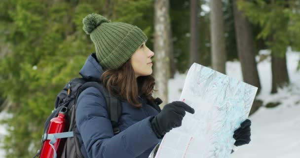 Krásná dívka na dovolené v horách se dívá na mapu tak, aby se neztratil a pochopit, kde to je. Koncept: orientace, silnice, cesty a úspěch